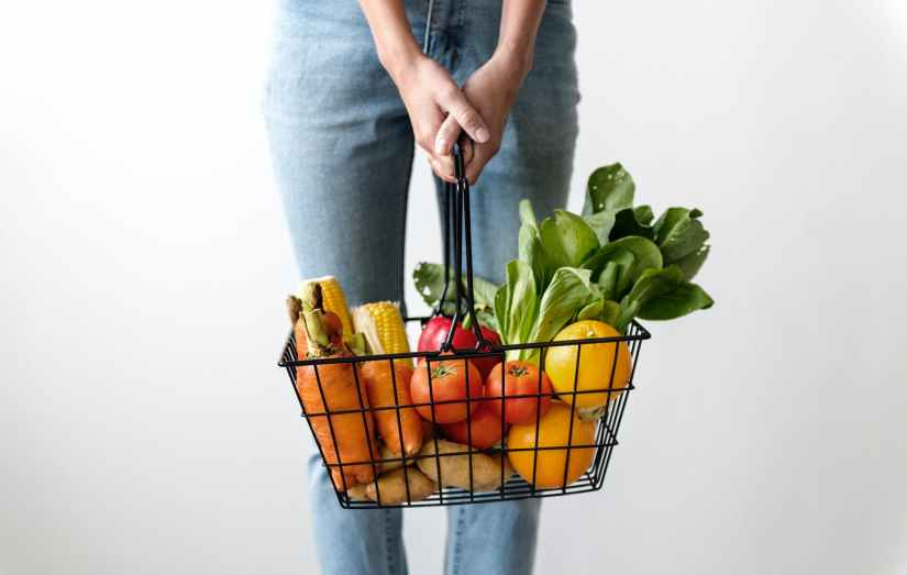 woman carrying basket of fruits and vegetables